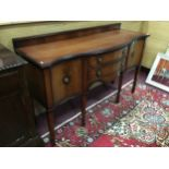 AN EDWARDIAN MAHOGANY SERPENTINE FRONTED SIDEBOARD