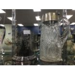 A CUT GLASS AND SILVER PLATED CLARET JUG, ALONG WITH A WINE COOLER CONTAINING BUTTONS AND COINS