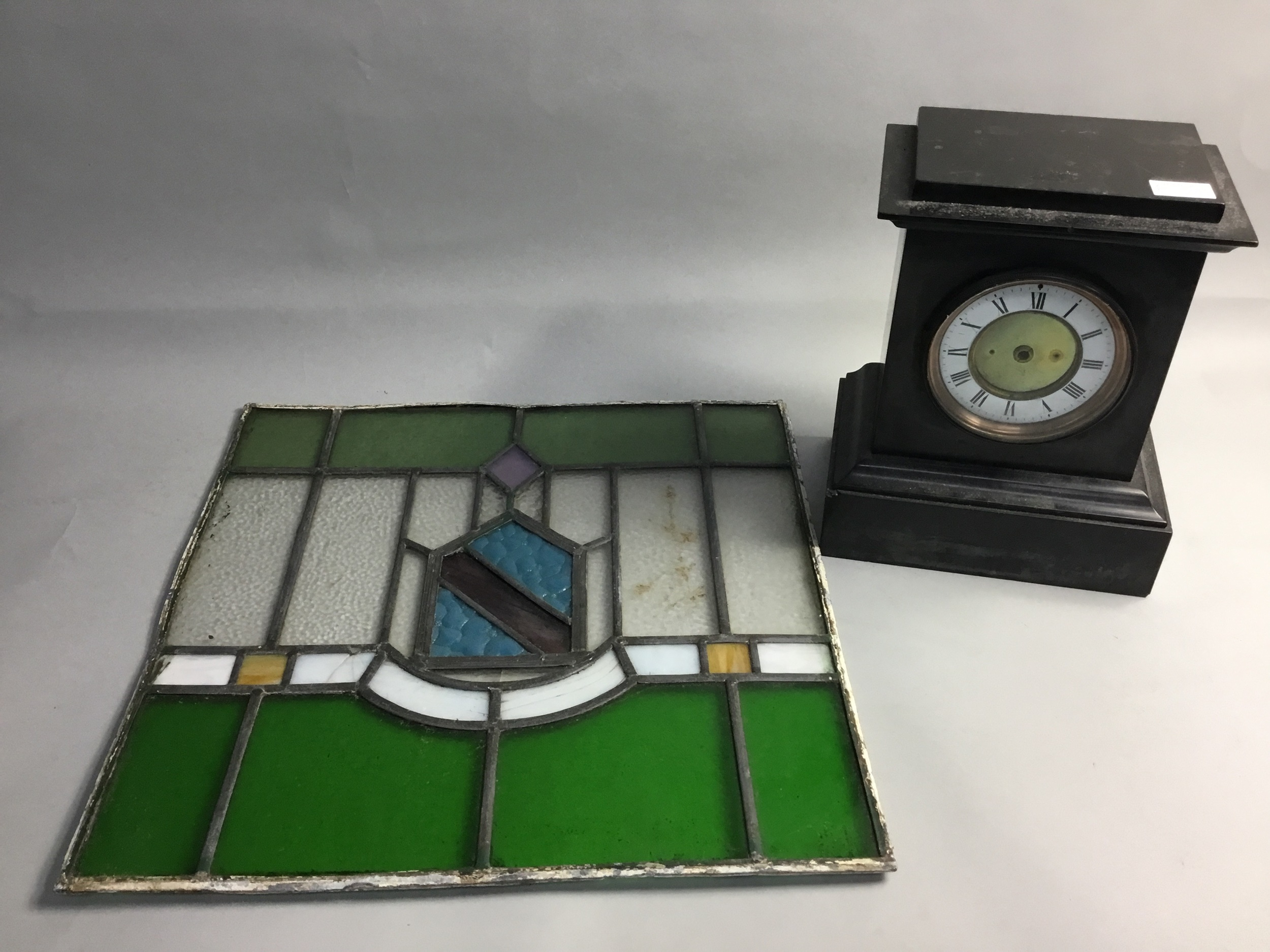 A BLACK SLATE MANTEL CLOCK, STAINED GLASS PANEL AND IRON BASKET