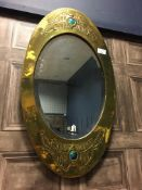 AN ARTS & CRAFTS BRASS AND ENAMEL MARQUISE SHAPED WALL MIRROR