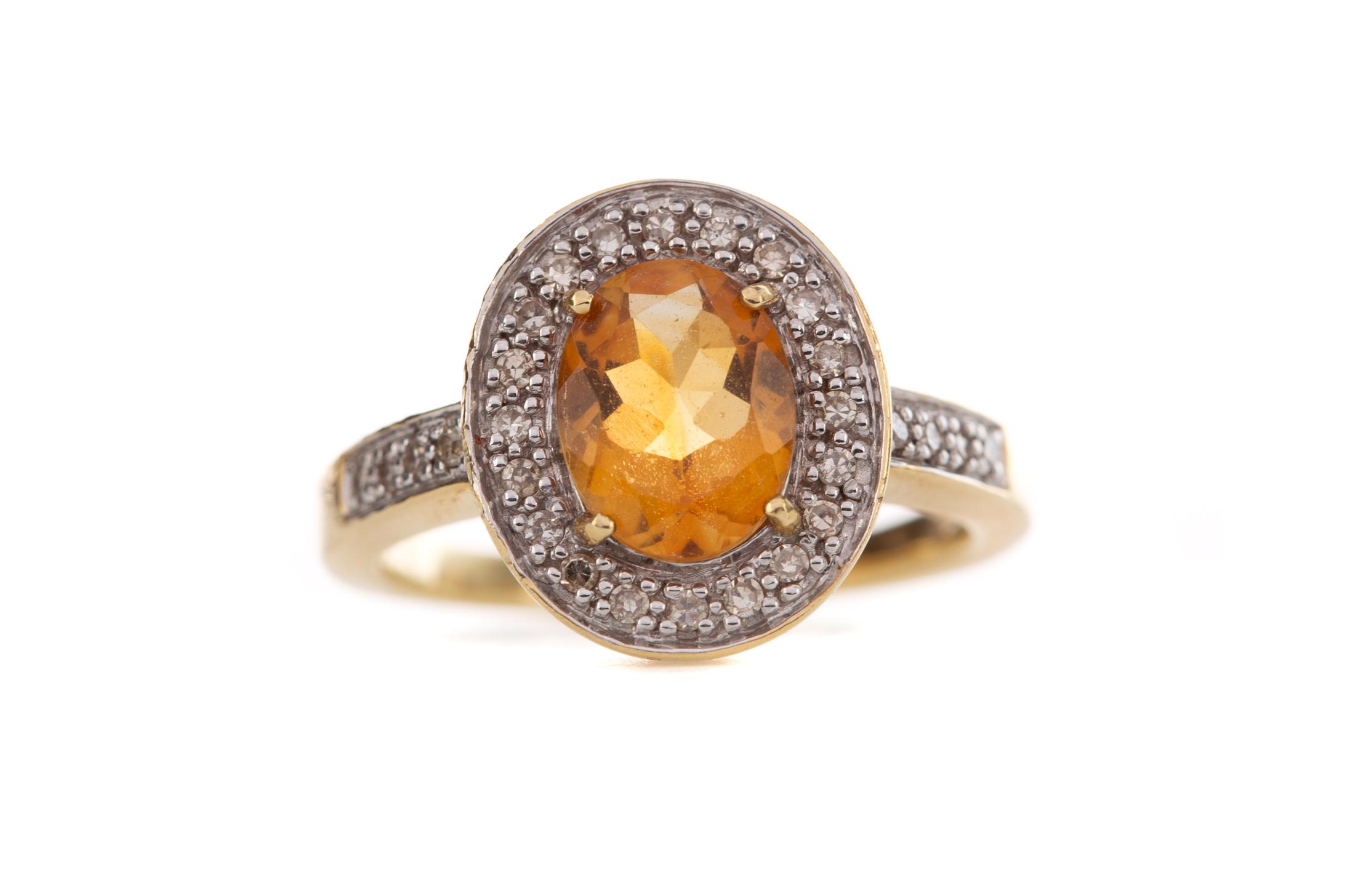AN ORANGE GEM SET AND DIAMOND RING