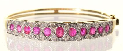 A RUBY AND DIAMOND BANGLE, LATE 20TH C, THE LINE OF LARGER GRADUATED RUBIES CENTRING A DIAMOND