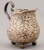 AN INDIAN SILVER REPOUSSE CREAM JUG, KUTCH, LATE 19TH C, ON THREE BALL FEET, 86MM H, 3OZS 8DWTS