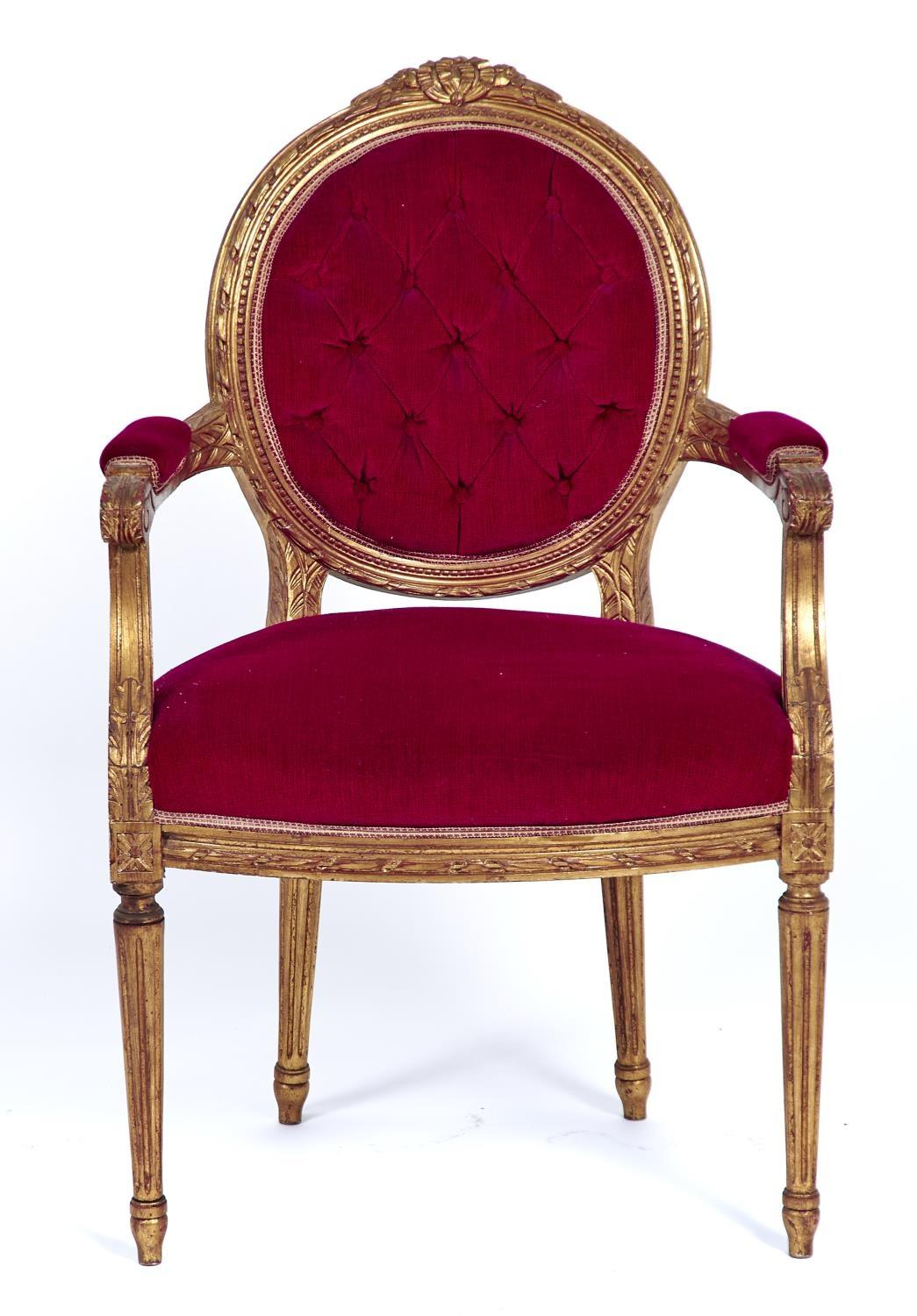 AN UPHOLSTERED GOLD PAINTED ELBOW CHAIR IN LOUIS XVI STYLE, LATE 20TH C, THE OVAL BACK CARVED RIBBON