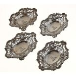 A SET OF FOUR VICTORIAN PIERCED SILVER BONBON DISHES, APPLIED WITH C SCROLLS AND SHELLS, ON