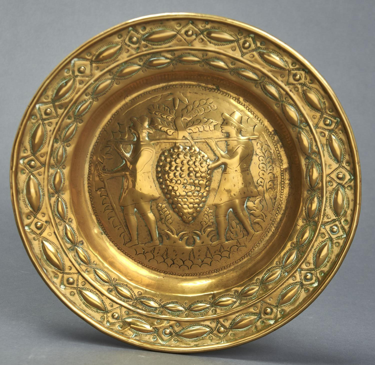A NUREMBERG BRASS ARMS DISH, 17TH / 18TH C, EMBOSSED TO THE CENTRE WITH WINE MAKERS, 40.5CM DIAM