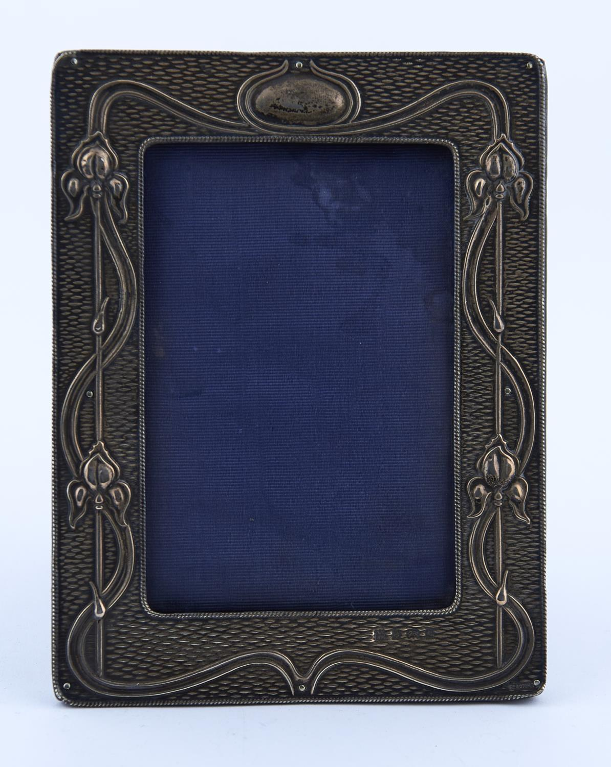 AN ART NOUVEAU SILVER PHOTOGRAPH FRAME, THE MOUNT DIE STAMPED WITH STYLISED LILIES AND ENTRELAC ON A