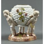 A PLAUE FLORAL ENCRUSTED BASKET SHAPED VASE, LATE 19TH C, SUPPORTED BY THREE PUTTI STANDING ON ROUND