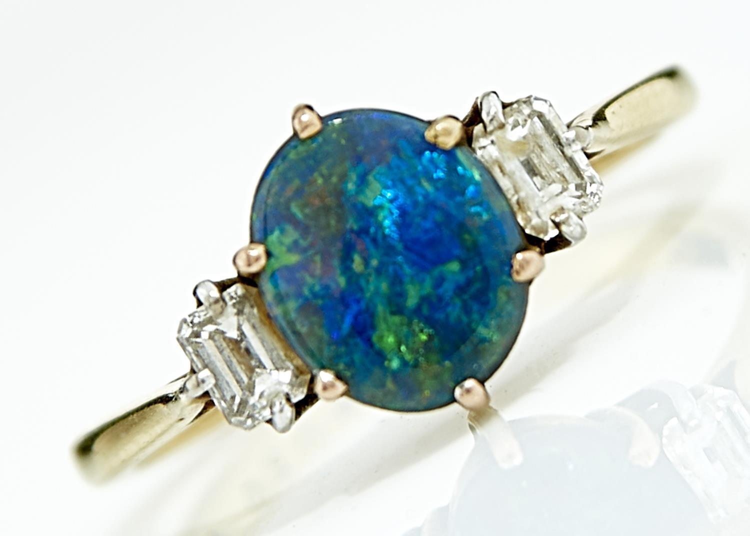 A BLACK OPAL AND DIAMOND RING. THE BLACK OPAL OF APPROX 7 X 9MM FLANKED BY BAGUETTE DAIMONDS IN 18CT