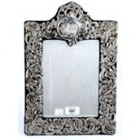 A GEORGE V SILVER DRESSING MIRROR, THE BEVELLED PLATE IN DIE STAMPED OPENWORK ROCOCO MOUNT WITH