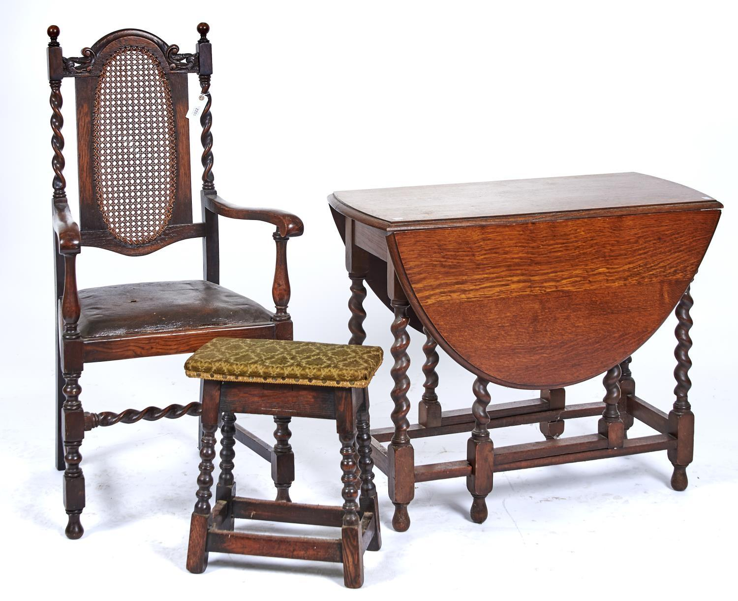 AN OAK OVAL GATELEG DINING TABLE, C1920, THE TOP WITH PAIR OF LEAVES ON BARLEY TURNED LEGS JOINED BY