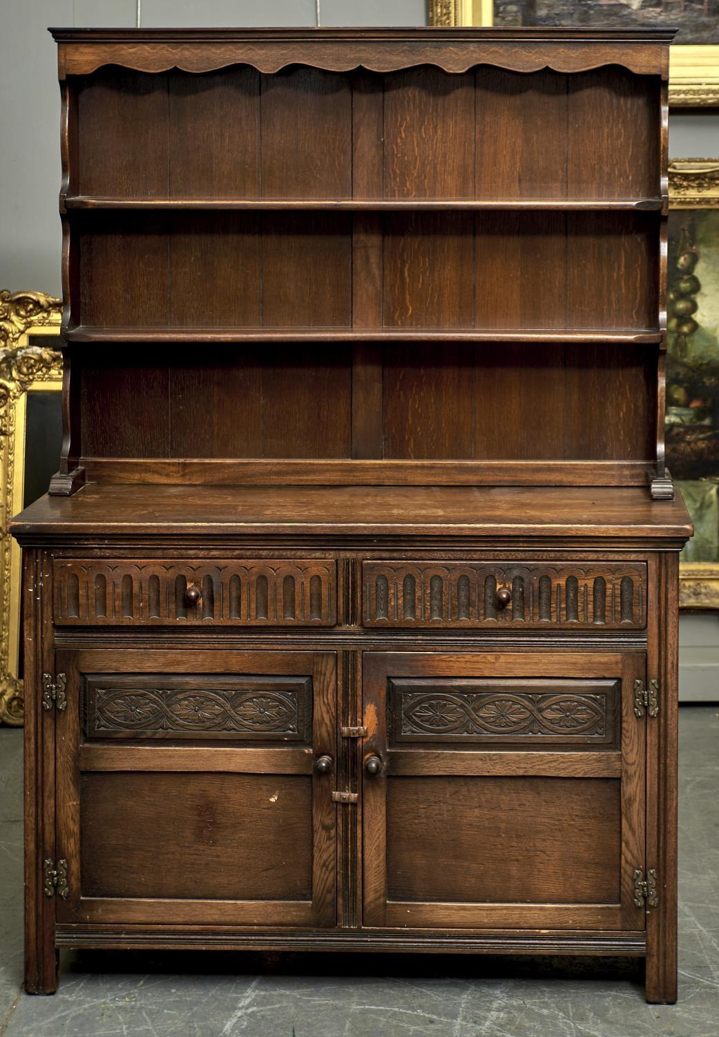 A REPRODUCTION OAK DRESSER IN SHALLOWED CORNICE, SHAPED FRIEZE, SHELVED BACK, THE PROJECTING BASE