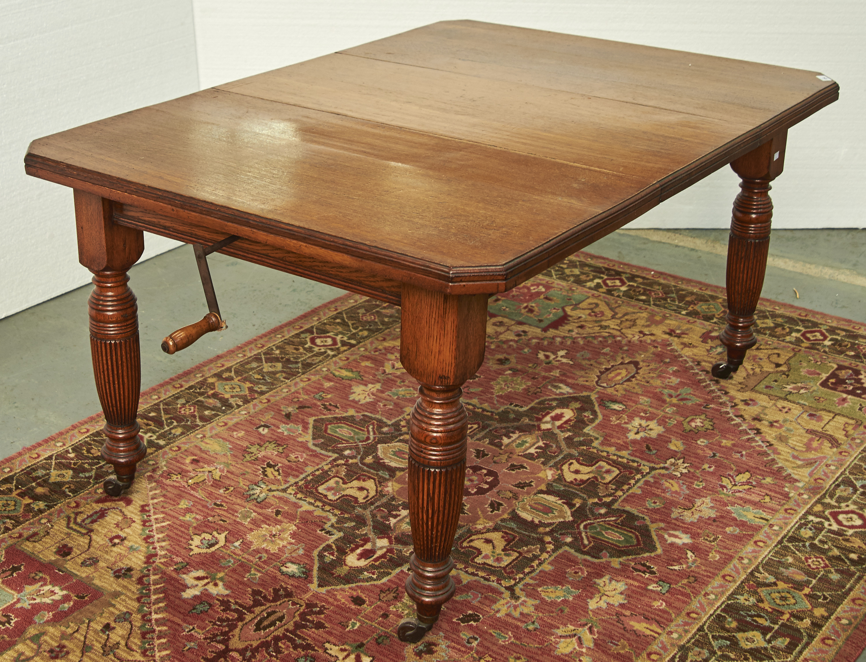 A VICTORIAN OAK EXTENDING DINING TABLE, C1880, CANTERED RECTANGULAR TOP ABOVE TURNED FLUTED LEGS