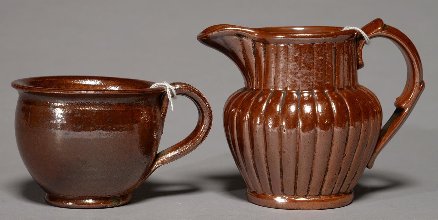 A DERBYSHIRE SALTGLAZED BROWN STONEWARE HANDLED POT OR PORRINGER AND A JUG, BOTH BRAMPTON,LATE
