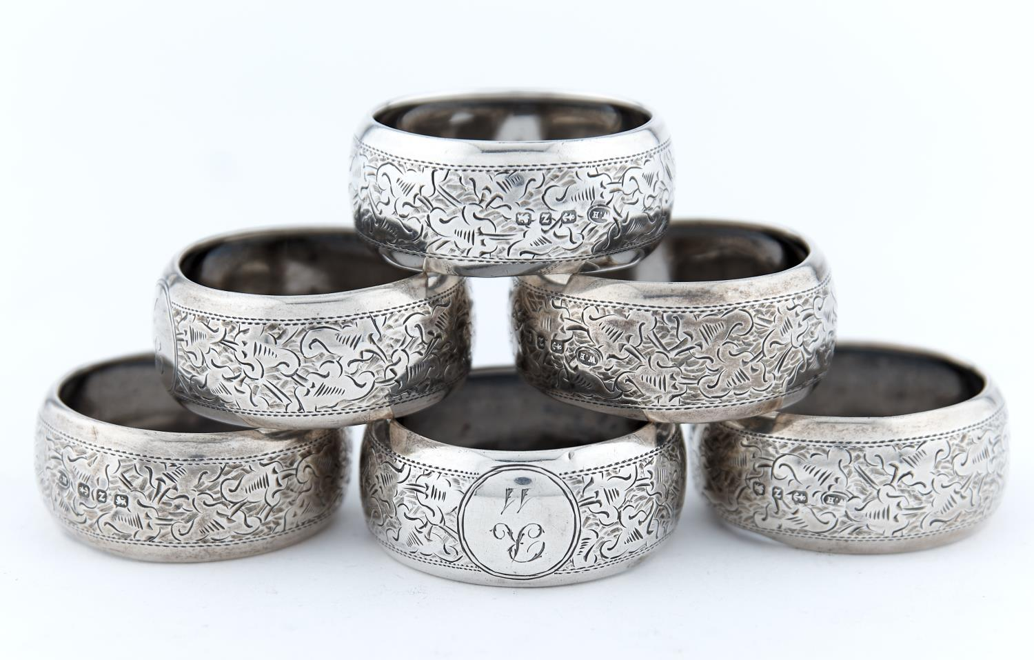 A PART SET OF SIX VICTORIAN SILVER NAPKIN RINGS, FOLIATE ENGRAVED, INITIALLED R AND NUMBERED, BY