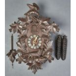 A GERMAN CARVED AND STAINED WOOD WALL HANGING CUCKOO CLOCK OF TYPICAL FORM, APPLIED WITH FOLIAGE AND