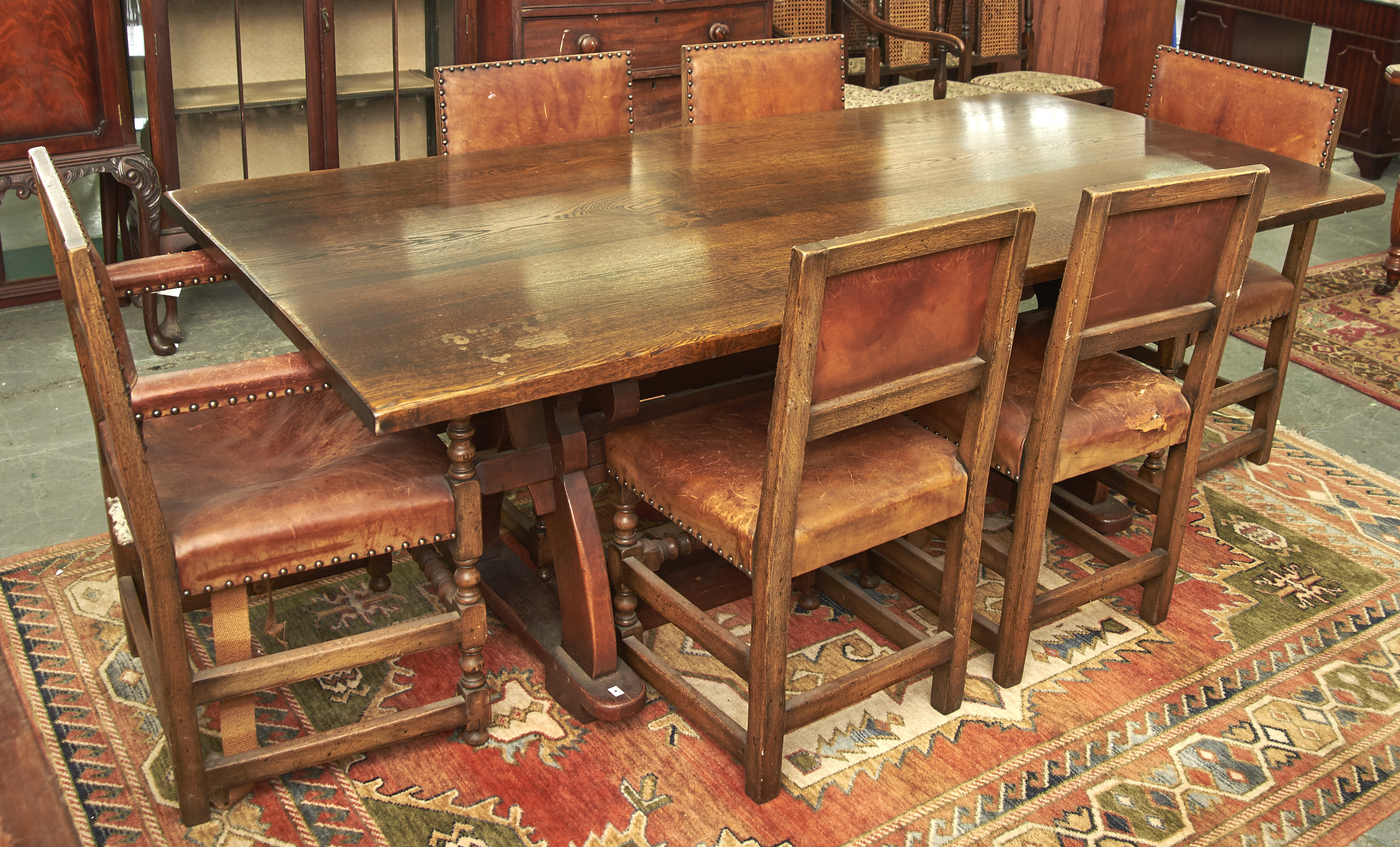 A REPRODUCTION OAK DINING TABLE OF TRESTLE FORM, THE RECTANGULAR TOP ABOVE YOLK STYLE TRESTLE ENDS