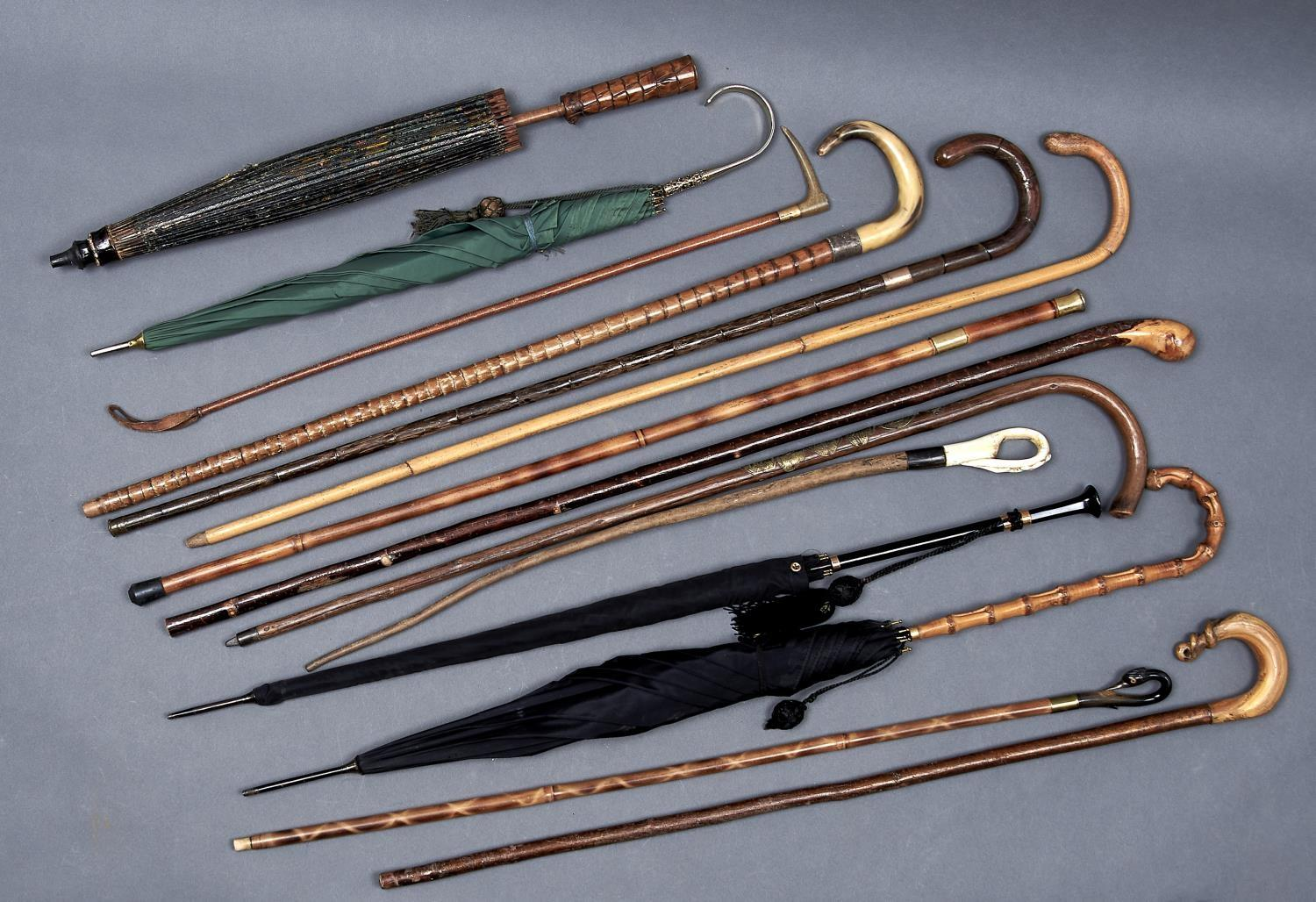 A COLLECTION OF WALKING CANES, STICKS AND PARASOLS, LATE 19TH - MID 20TH C, INCLUDING A 9CT GOLD