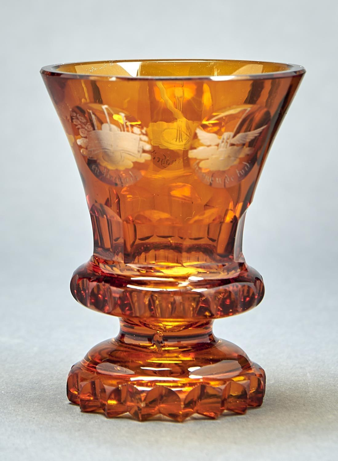 A BOHEMIAN FACETED AND AMBER FLASHED GLASS BEAKER, MID 19TH C, THE FLARED BOWL ENGRAVED WITH FIVE