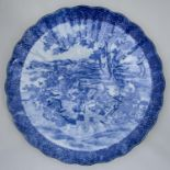 A JAPANESE FLUTED BLUE AND WHITE IMARI DISH, EARLY 20TH C, TRANSFER PRINTED WITH FIGURES IN