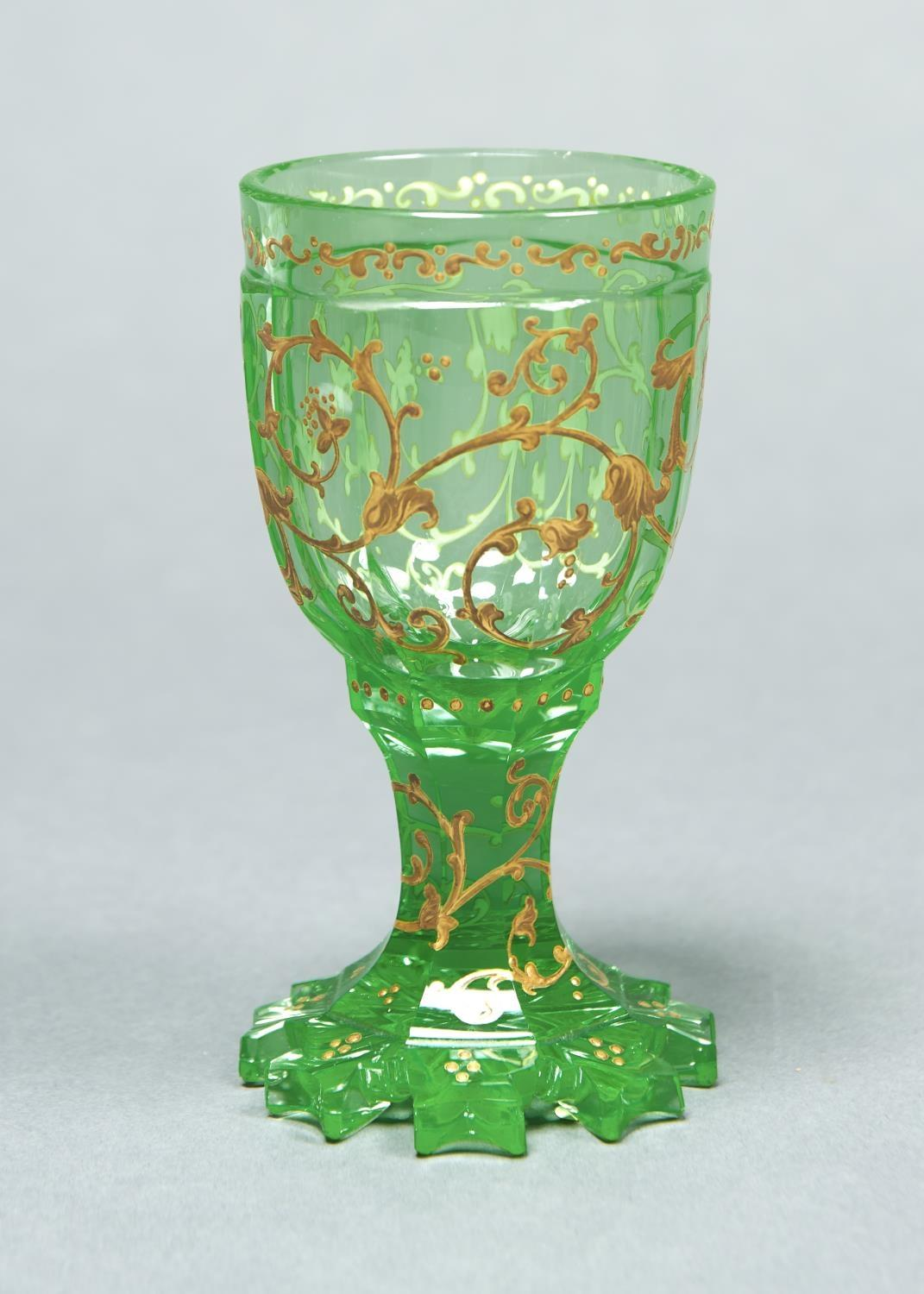 A BOHEMIAN GREEN GLASS GOBLET, C1860, THE FACETED BOWL AND WAISTED STEM WITH RAISED GILT SCROLLING
