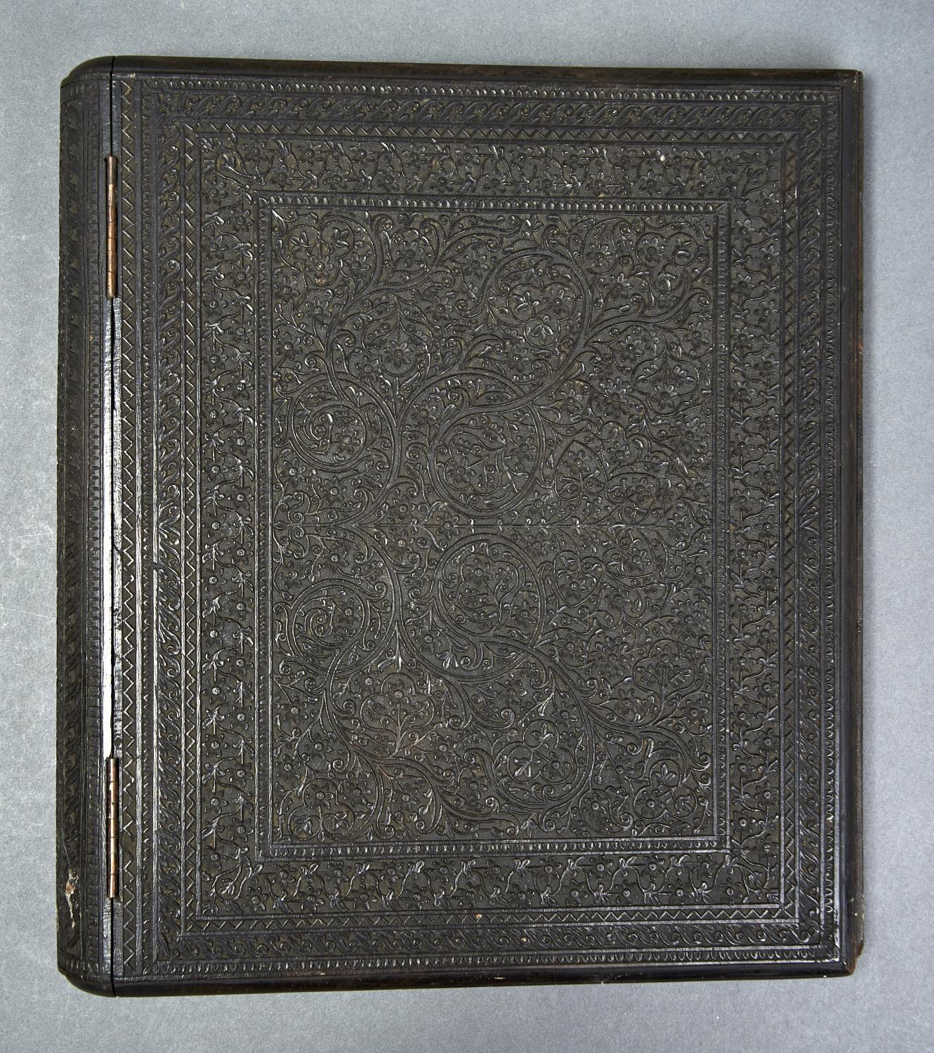 A CARVED EBONY BLOTTING BOOK, 19TH C,  WITH TENDRILS WITHIN CONFORMING FOLIATE PALMETTE BORDERS,