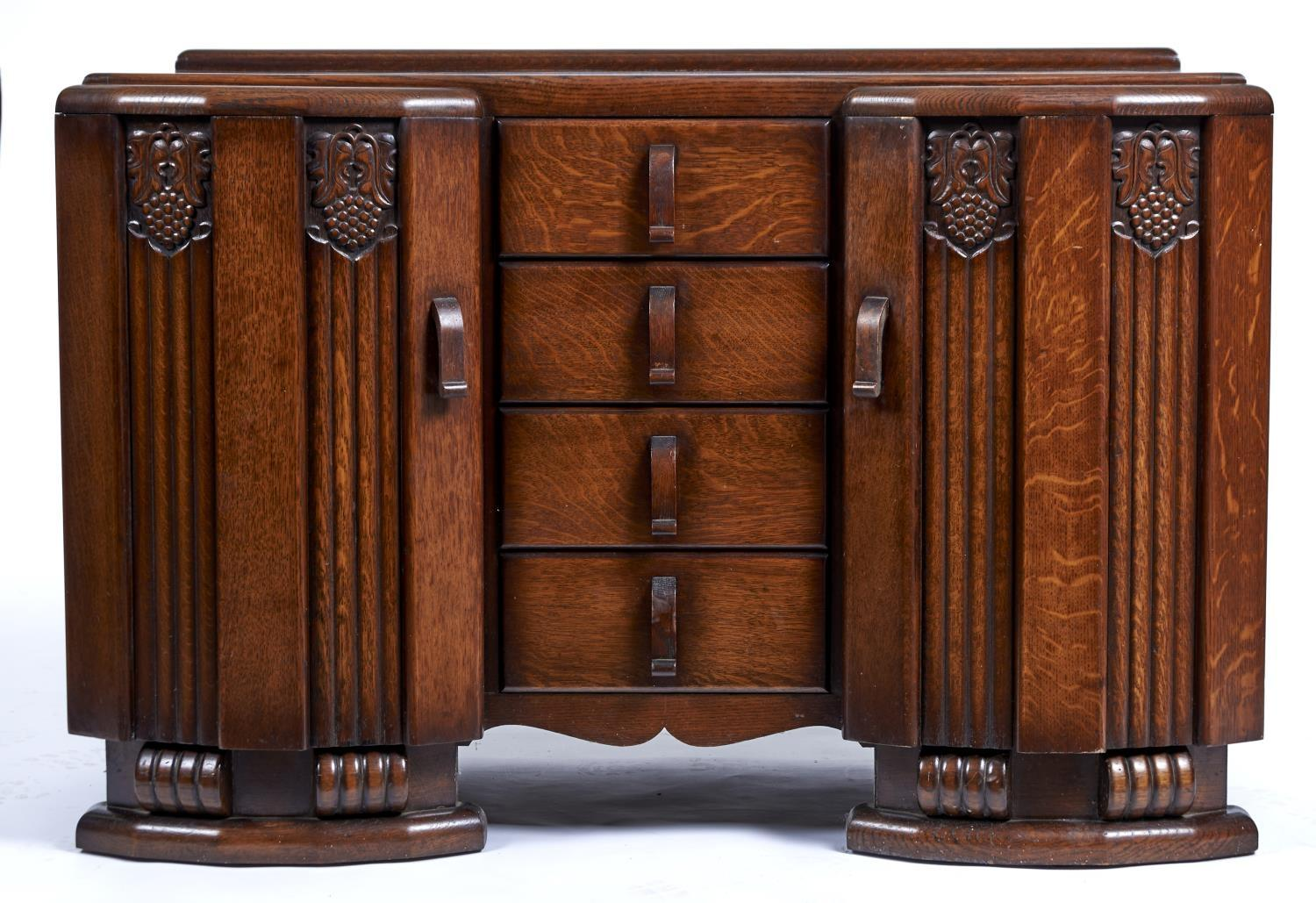 AN ART DECO STYLE OAK SIDEBOARD, C1950, WITH PROJECTING PANELLED FLUTED CUPBOARDS CARVED TO THE