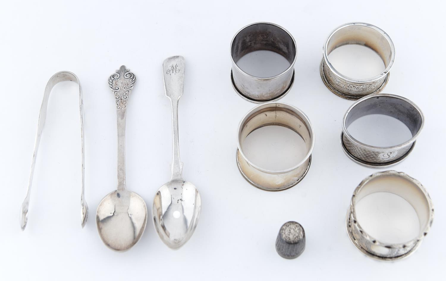 FIVE EDWARDIAN AND LATER SILVER NAPKIN RINGS, A BRITANNIA STANDARD REPLICA LACE BACK SPOON, A