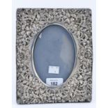 AN EDWARDIAN SILVER PHOTOGRAPH FRAME, THE OVAL APERTURE TO THE DIE STAMPED MOUNT SURROUNDED BY A