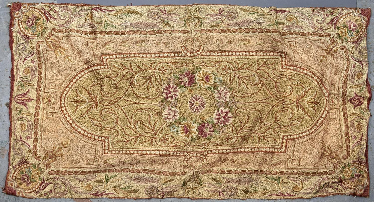 A CREWEL WORK PANEL OR RUG, DECORATED TO THE CENTRE WITH A FLORAL ROUNDEL WITHIN ARCHED FRAME, THE