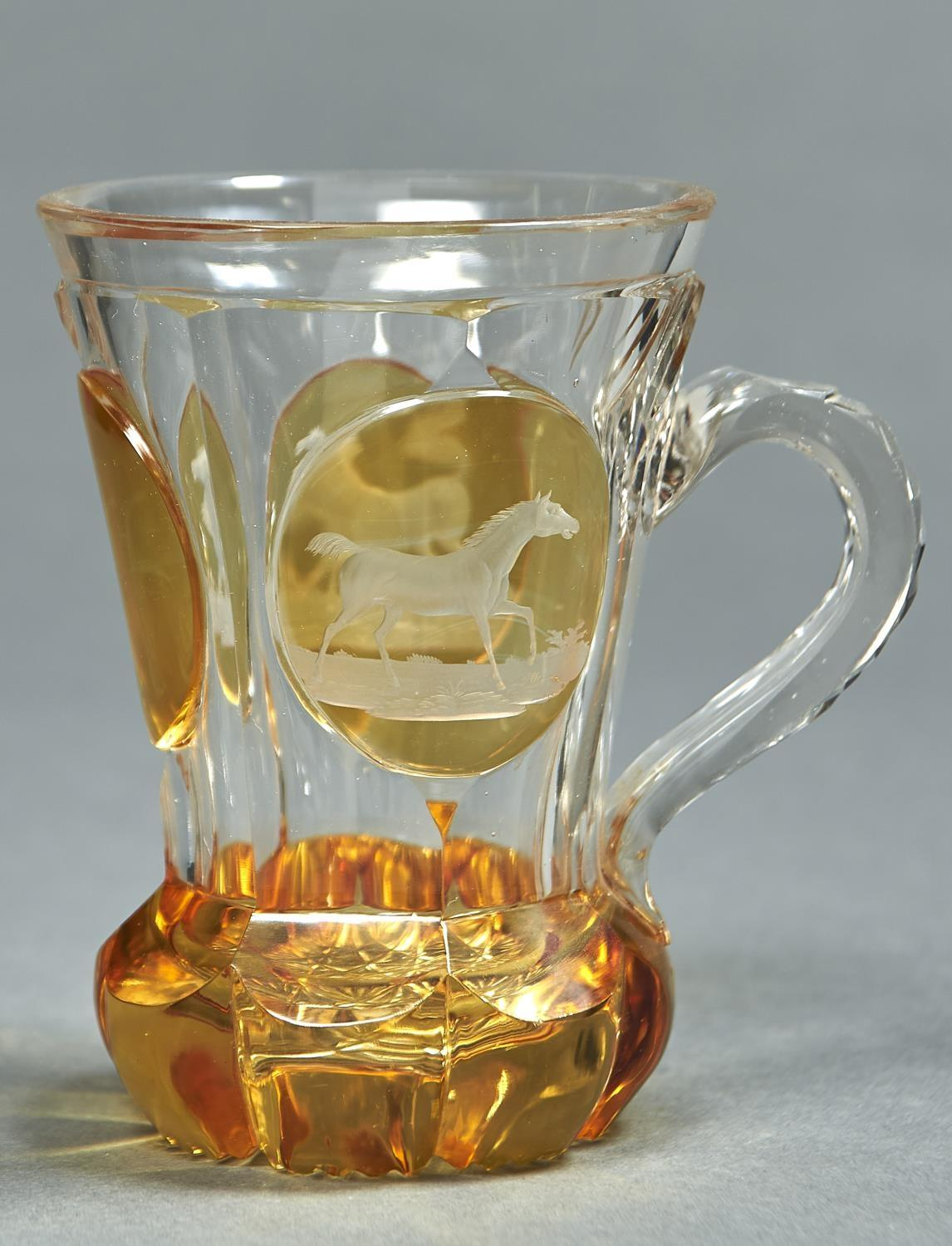 A BOHEMIAN AMBER FLASHED GLASS MUG, C1860, ENGRAVED TO EITHER SIDE WITH A HORSE, 13CM H Good