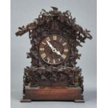 A GERMAN CARVED AND STAINED WOOD CUCKOO CLOCK, LATE 19TH C, OF TYPICAL FORM WITH TILED, PITCHED ROOF