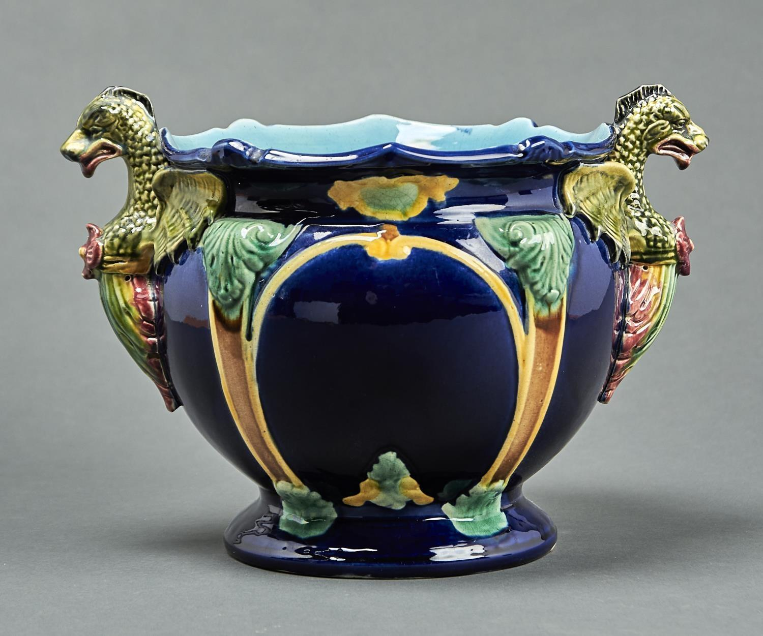 A STAFFORDSHIRE DRAGON HANDLED MAJOLICA JARDINERE, C1880, MOULDED WITH STRAPWORK ON A COBALT