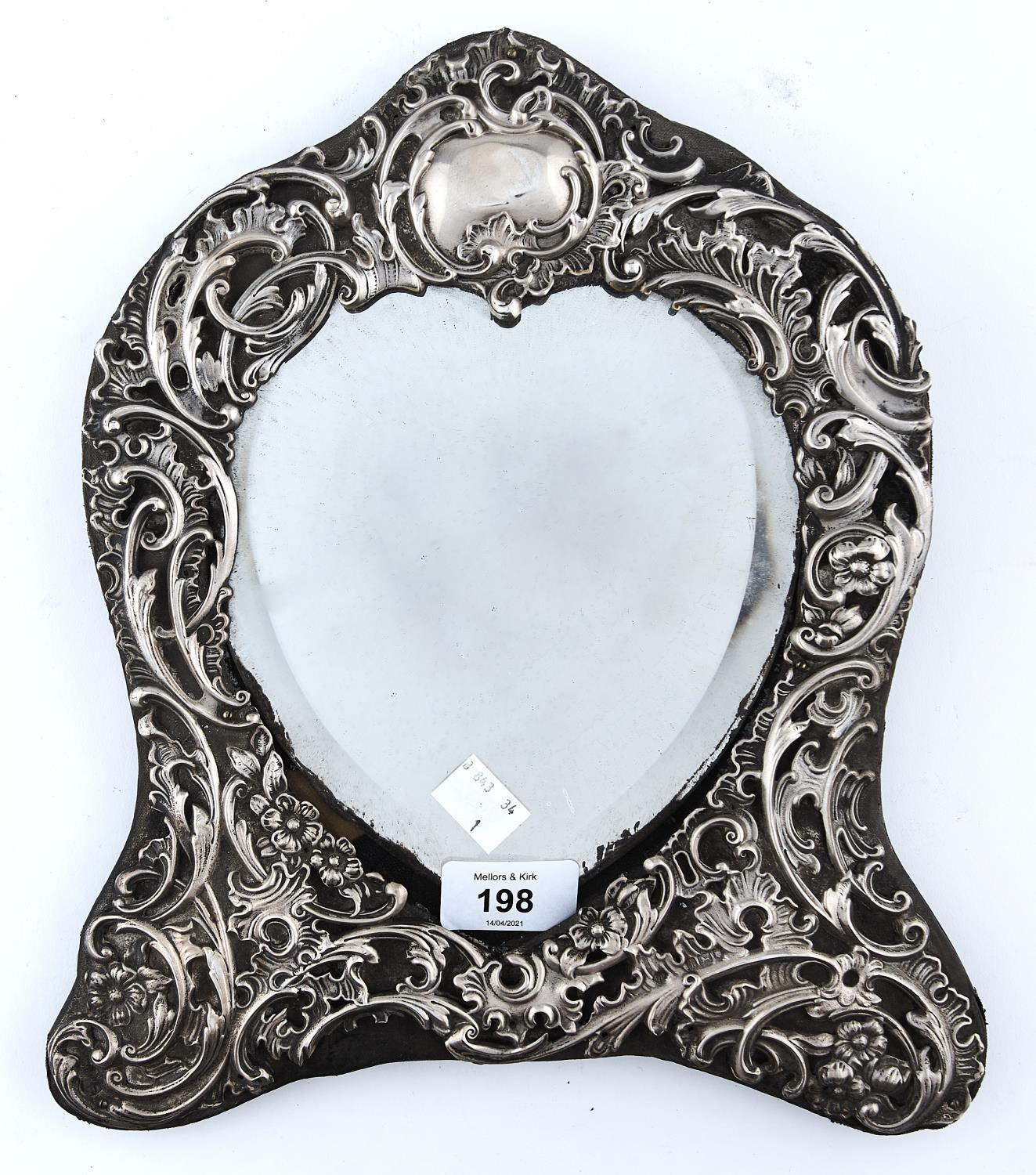 AN EDWARD VII SILVER DRESSING MIRROR, THE HEART SHAPED BEVELLED PLATE IN DIE STAMPED OPENWORK ROCOCO