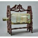 A VINTAGE SHIP IN A BOTTLE, THREE MASTED SCHOONER CONTAINED WITHIN A BOTTLE WITHIN A FRET CUT FRAME,