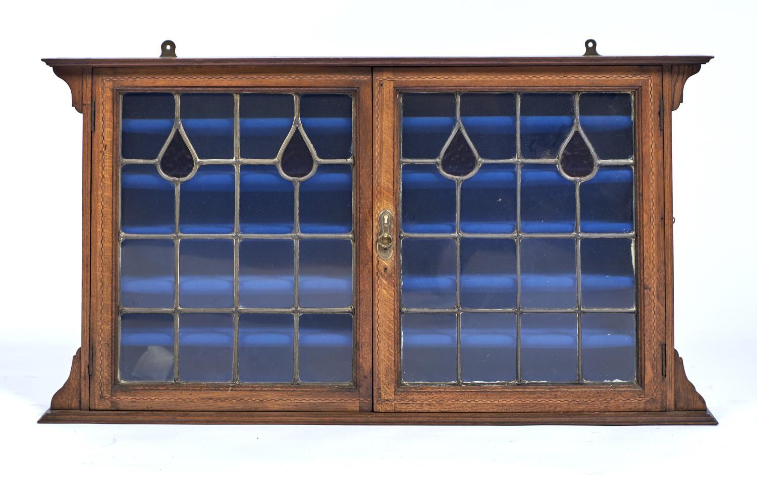 AN OAK ARTS AND CRAFTS WALL CABINET, C1890, THE PROJECTING CORNICE ABOVE A PAIR OF DOORS PARQUETRY