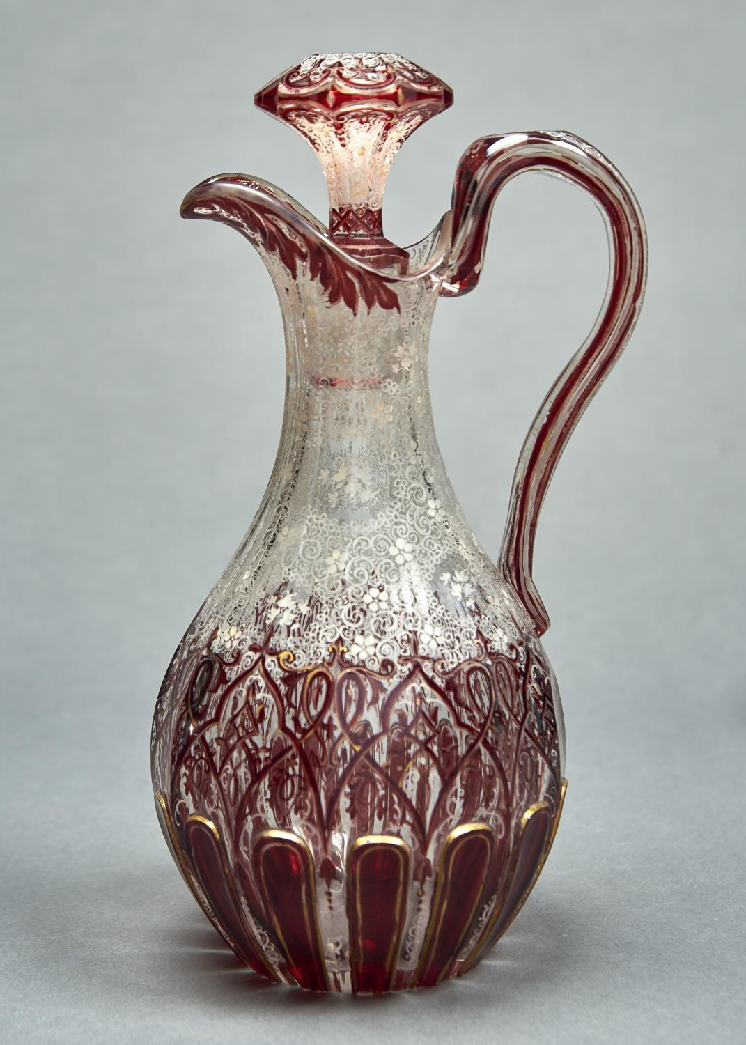 A RUBY FLASHED AND WHITE ENAMELLED GILT GLASS CLARET JUG AND STOPPER, C1860, 29CM H Typical handling