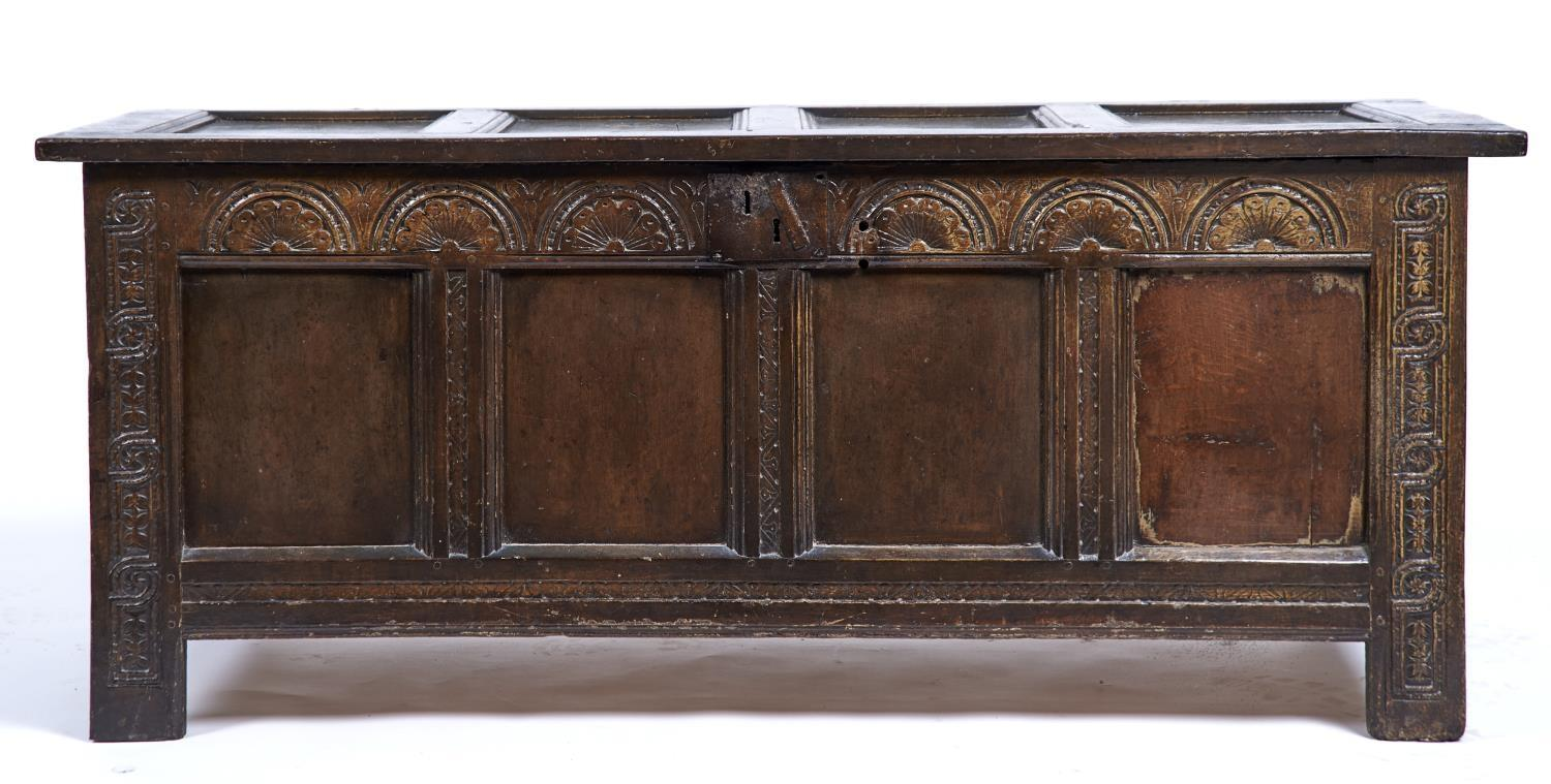 AN OAK BLANKET BOX WITH CARVED FRIEZE AND GUILLOCHE AND LEAF CARVED UPRIGHTS, THE FRAME
