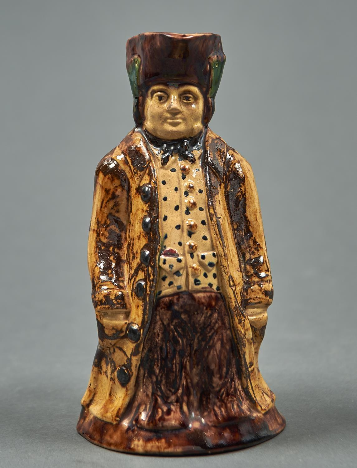 A MANGANESE GLAZED BUFF EARTHENWARE TOBY JUG, MID 19TH C, THE FIGURE STANDING WITH HANDS IN HIS COAT