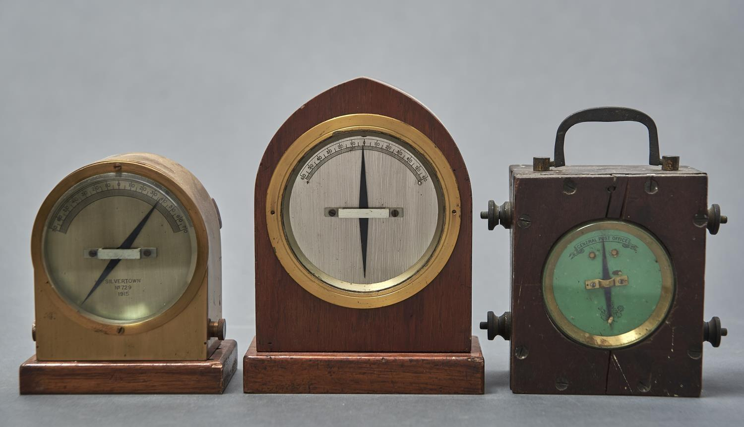 A LANCET ARCHED MAHOGANY CASED GALVANOMETER, ANOTHER IN LACQUERED BRASS CASE, DIAL MARKED