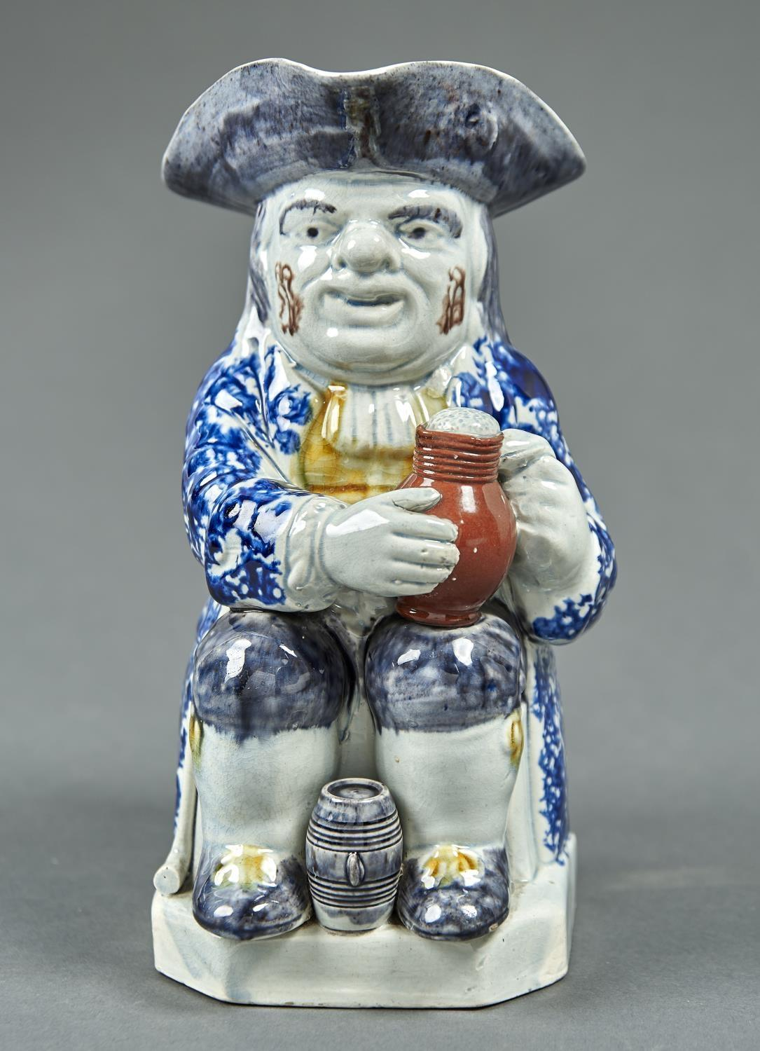 A PRATT WARE TOBY JUG, C1800, THE SEATED FIGURE HOLDING A FOAMING JUG OF ALE, A SMALL BARREL BETWEEN