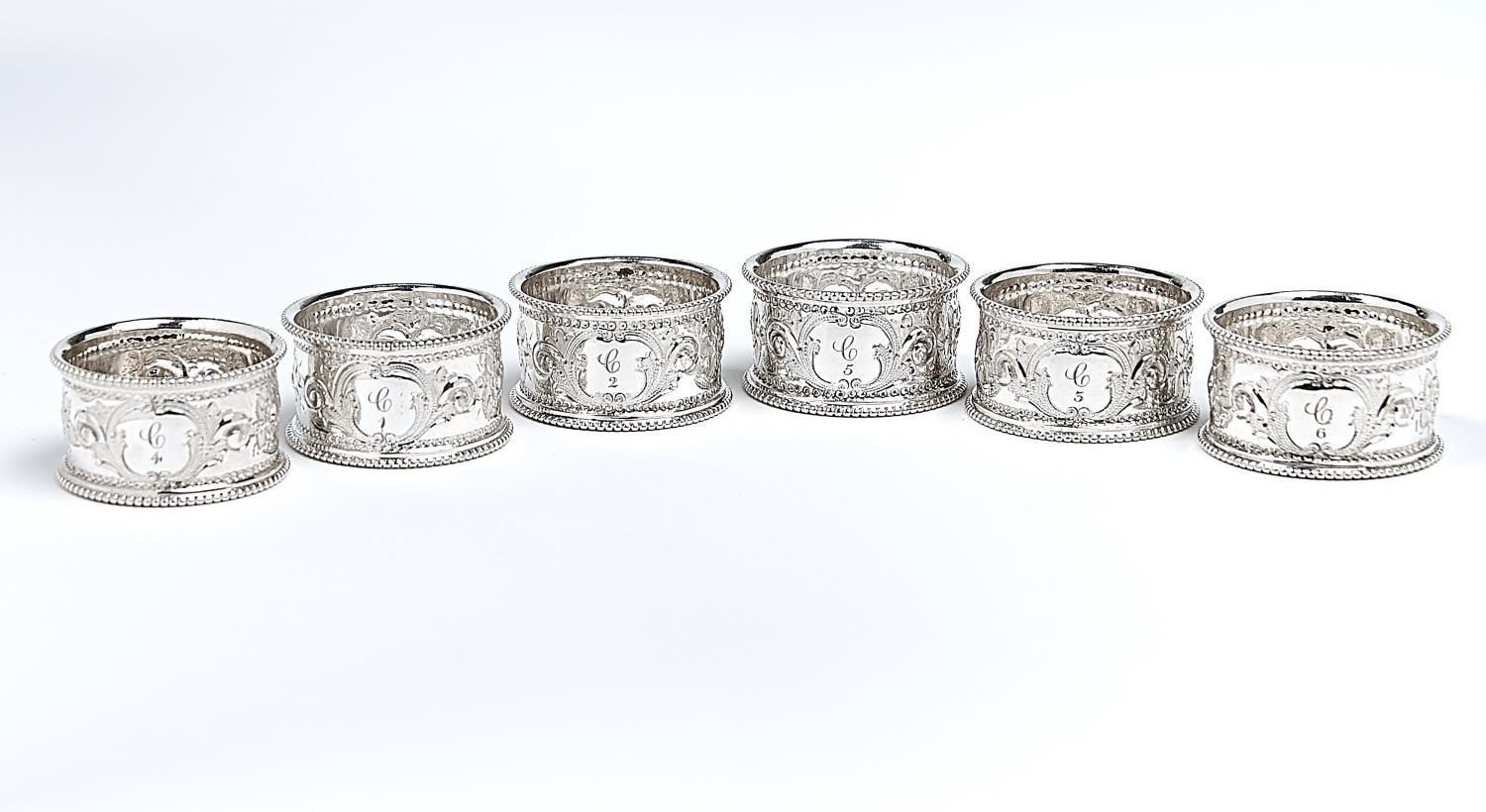 A SET OF SIX VICTORIAN EPNS BEADED NAPKIN RINGS, C1870, EMBOSSED WITH FOLIAGE, NUMBERED 1-6, PLUSH