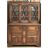 AN OAK DRESSER, MOULDING ABOVE THREE LEAD GLAZED DOORS WITH SHELVED INTERIOR, THE PROJECTING BASE