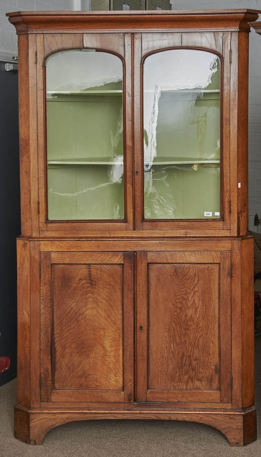 A LARGE GEORGE IV OAK STANDING CORNER CABINET, C1830, FLARED CAVETTO CORNICE ABOVE A PAIR OF
