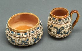 A Doulton ware cream jug and sugar bowl, by Francis E Leigh, decorated with white flowerheads and