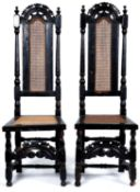 A pair of Queen Anne walnut high back caned chairs, c1700, with pierced arched cresting rails