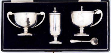 A George V silver trophy shaped condiment set, pepperette 82mm h, by William Adams Ltd, Birmingham