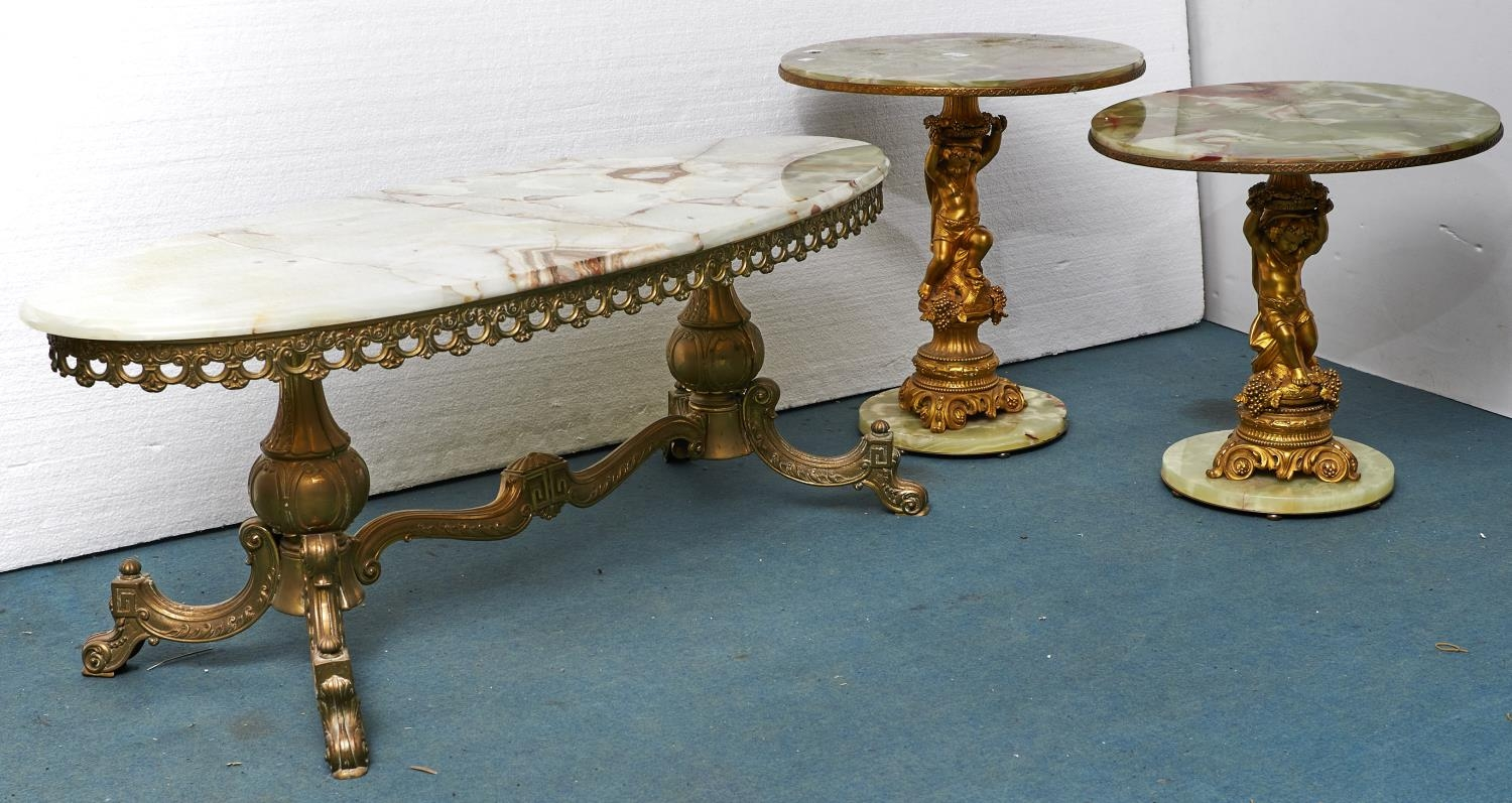 Two similar giltmetal and onyx putto figural pedestal tables and an oval giltmetal table with onyx