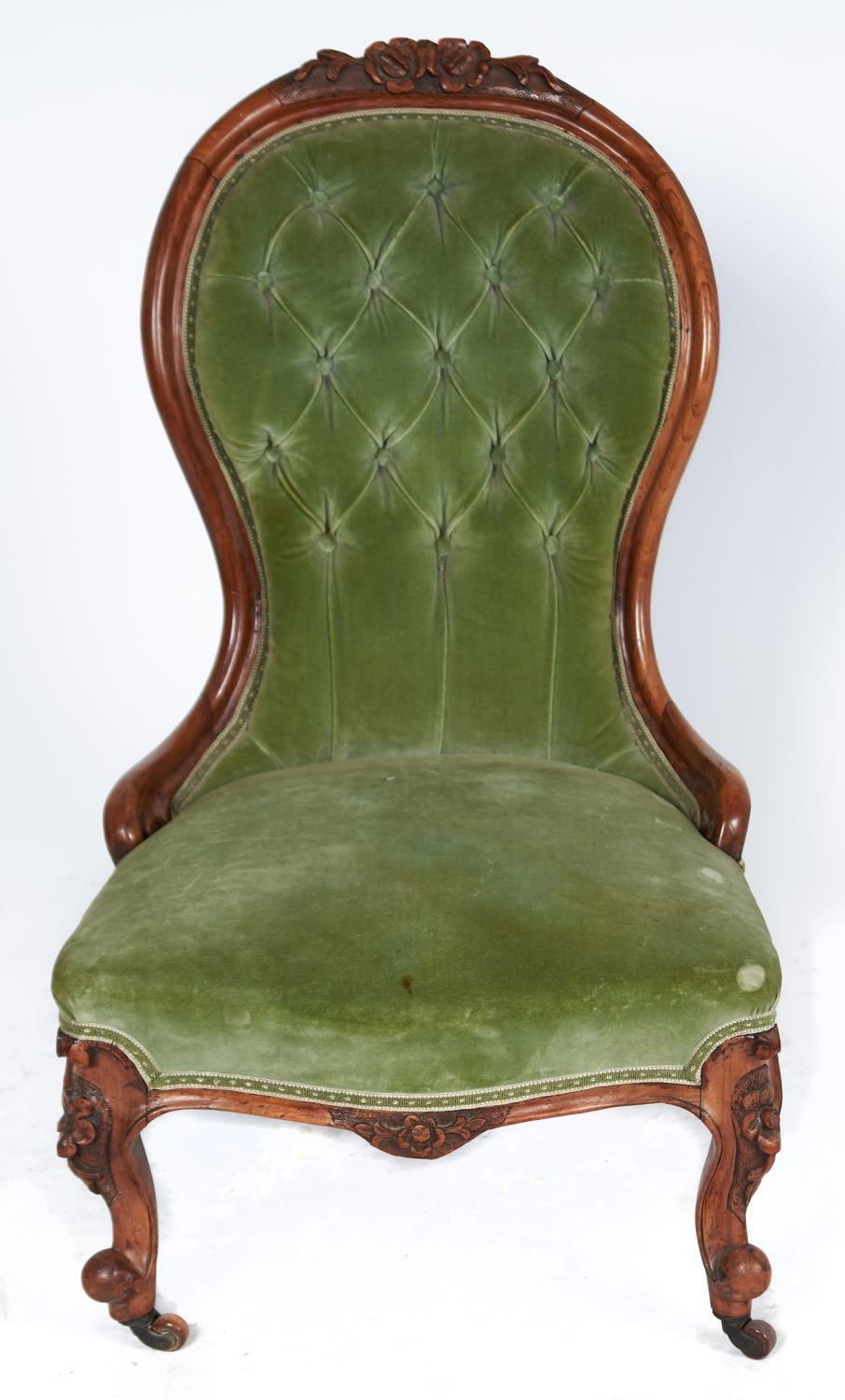 A Victorian walnut nursing chair, c1870, the top rail carved with flowerheads and leafage on a