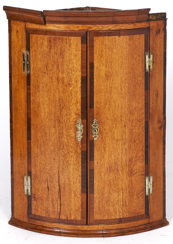 A George III inlaid oak bow fronted corner cupboard, 95cm h x 70cm w Shrinkage cracks to one door,